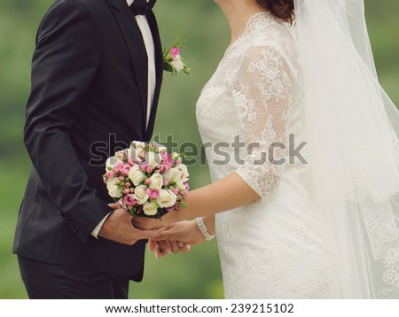 kissing bride and groom in park - stock photo