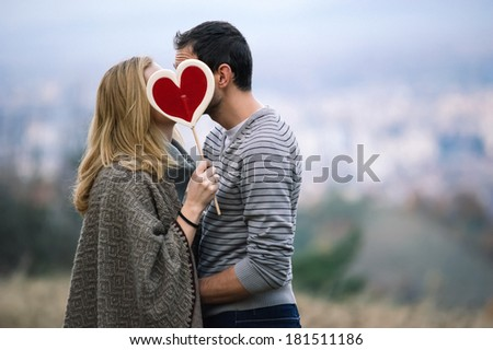 Kissing couple holding a candy heart - stock photo