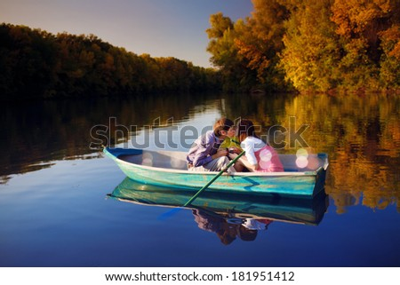 Kissing couple in a boat. - stock photo