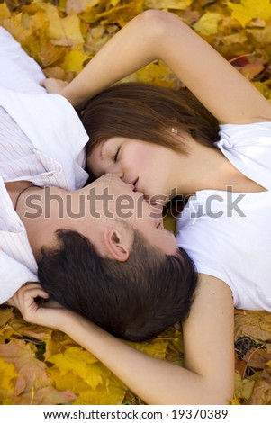 kissing couple in autumn park - stock photo