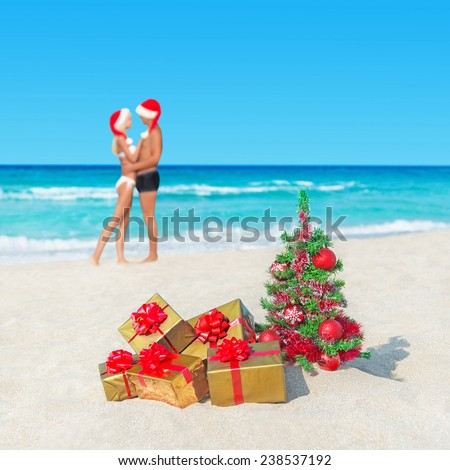 Kissing couple in santa hats at tropical  beach with christmas tree and packed golden gifts - New Years vacation in hot countries concept - stock photo