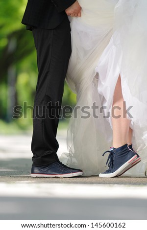 kissing couple in sneakers in park - stock photo