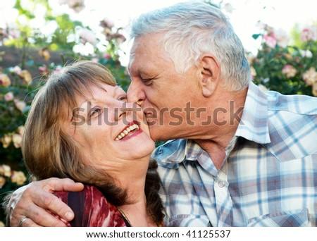 Kissing happy elderly couple in love outdoor - stock photo