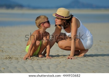 Kissing his mom: young beautiful woman dressed in white with a hat crouched in the sand beside her son, they interact lovingly and tenderness looking at each other - stock photo