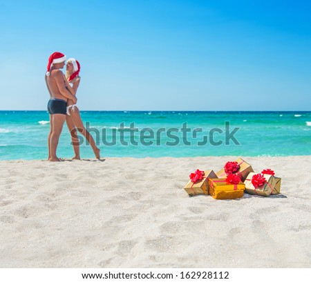 kissing lovers couple in santa hats at sea beach with christmas packed  golden gifts and red bows - stock photo