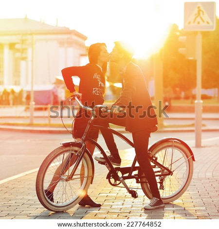Kissing romantic couple in love. Sunset. Boy and girl standing near a vintage bike in urban scene - stock photo