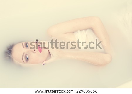 kissing spa finger: portrait of lying in the milk water beautiful tender young blond woman having fun posing sensually & looking at camera on light copy space background - stock photo