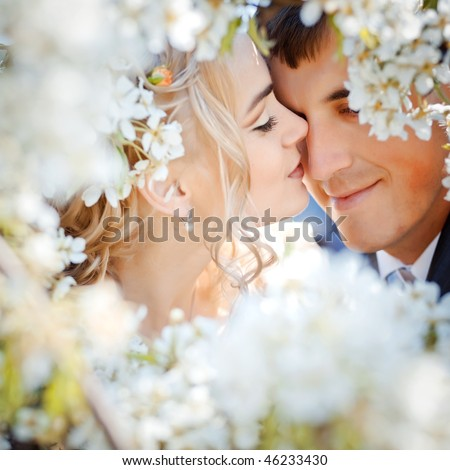 Kissing wedding couple in spring nature close-up portrait - stock photo