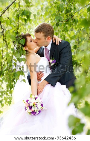 Kissing wedding couple in summer nature - stock photo