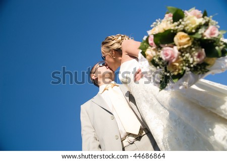 kissing wedding pair isolated on blue sky