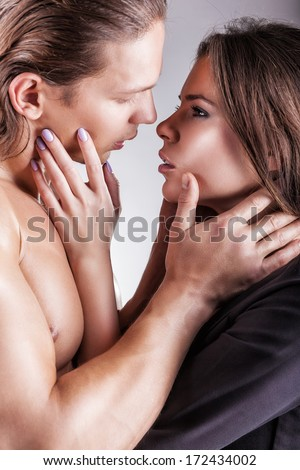 Kissing young couple on a gray background