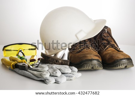 Kit of tools and equipments used by an electrician. There are a hard hat, a protective gloves, pliers, protective goggles, screwdriver, hammer and a gaiter. Everything in a white background. - stock photo