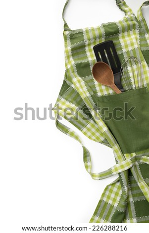 Kitchen apron and utensils - stock photo