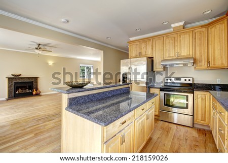 Kitchen area in empty house. Kitchen island with granite top and empty living room with fireplace