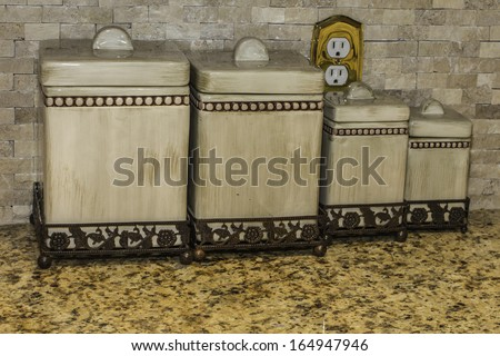Kitchen canisters sitting on top of a granite counter top. - stock photo