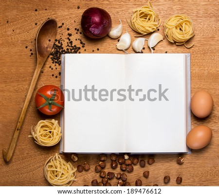 Kitchen. Cooking book and food on the table - stock photo