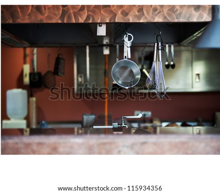 Kitchen cooking utensils on hook against - stock photo