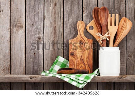 Kitchen cooking utensils on shelf against rustic wooden wall with copy space - stock photo