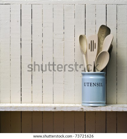 Kitchen cooking utensils; wooden spatulas etc in china storage pot; on wooden shelf against rustic kitchen wall; excellent copy space over wall area - stock photo