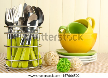 Kitchen cutlery in metal stand with clean dishes on tablecloth on beige background - stock photo