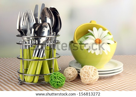 Kitchen cutlery in metal stand with clean dishes on tablecloth on bright background - stock photo