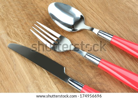 Kitchen cutlery on wooden table - stock photo