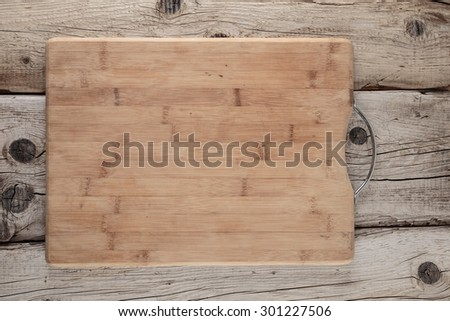 kitchen cutting board on an old wooden table - stock photo