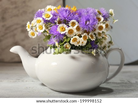 Kitchen decoration with teapot and wild flowers on wooden background - stock photo