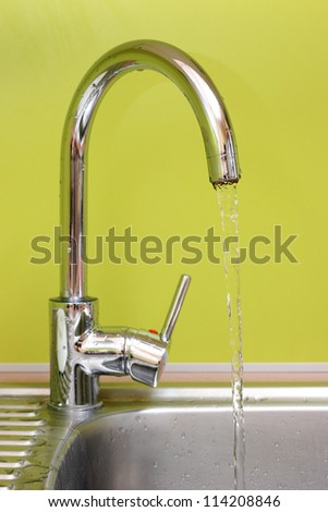 kitchen faucet and sink with running water - stock photo