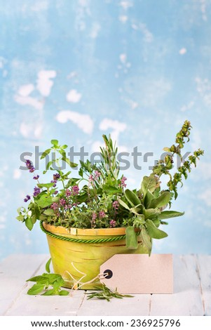 Kitchen herbs in natural basket on a wooden table - stock photo
