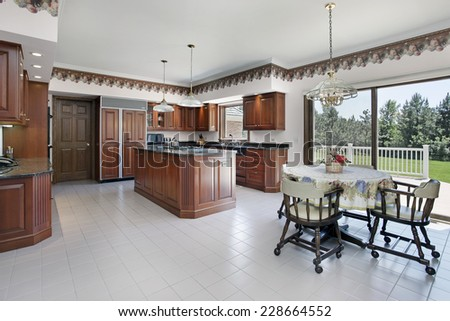 Kitchen in luxury home with cherry wood cabinetry - stock photo