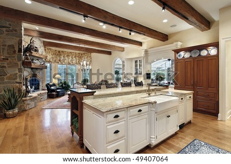 Kitchen in luxury home with stone fireplace - stock photo