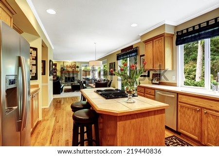 Kitchen in luxury house. Kitchen island with built-in stove and two stools, decorated with fresh tulips