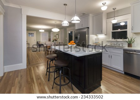 Kitchen in modern home with white Marble counter tops wooden floor and all new appliances with glimpse into dining area and living room. - stock photo