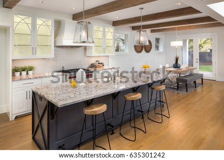 Kitchen in New Luxury Home with Large Island, Hardwood Floors, Range Hood, and Glass Fronted Cabinets, Horizontal Orientation. Lights are On