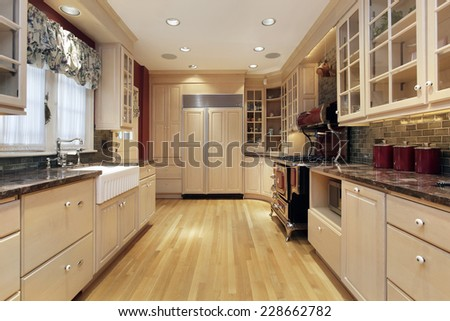 Kitchen in suburban home with oak wood cabinetry - stock photo