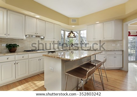 Kitchen in suburban home with white cabinetry - stock photo