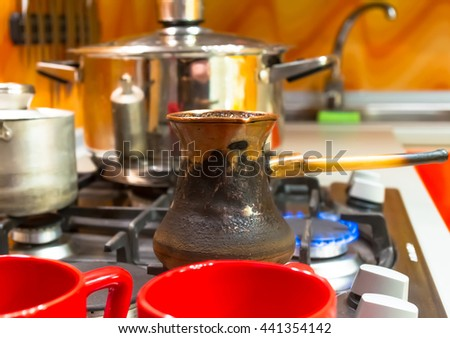 kitchen interior - cooking coffee in Arabic in traditional copper cezve on a gas stove - stock photo