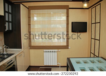 Kitchen interior design residential apartments. Yellow-brown curtains in the kitchen room and yellow wallpaper on the walls