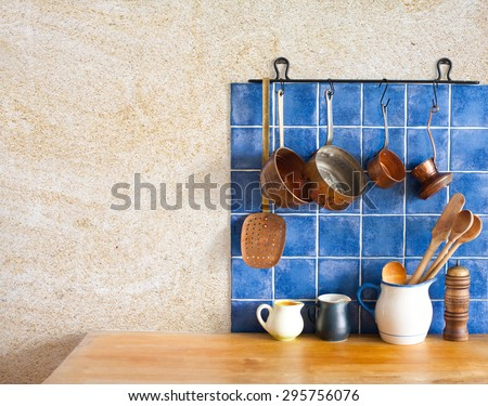 Kitchen interior. Hanging retro design copper kitchenware set. Pots, stewpots, coffee maker, spoon, skimmer. Different sizes, colors pitchers on the wooden table. Blue tiles, aged sand wall texture. - stock photo