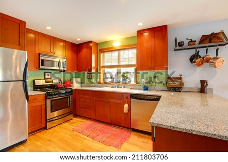 Kitchen interior with granite tops, green back splash and ss-appliances - stock photo