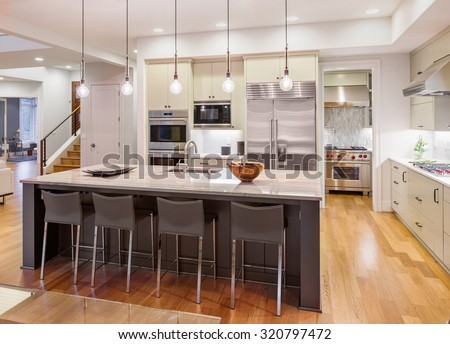 Kitchen Interior with Island, Sink, Cabinets, and Hardwood Floors in New Luxury Home - stock photo