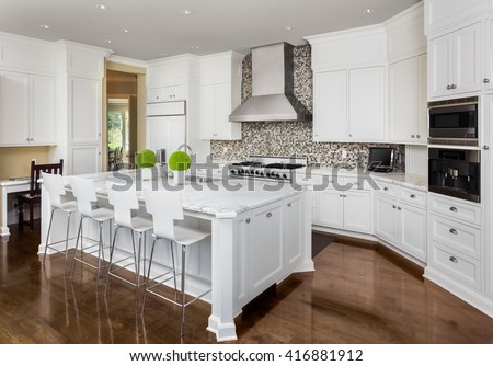 Kitchen Interior with Island, Sink, Cabinets, Oven, Range, and Hardwood Floors in New Luxury Home - stock photo