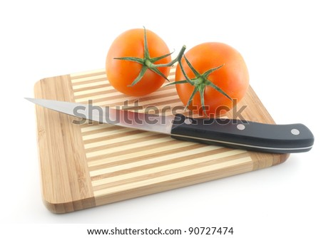 Kitchen-knife and red tomatoes on the preparation board - stock photo