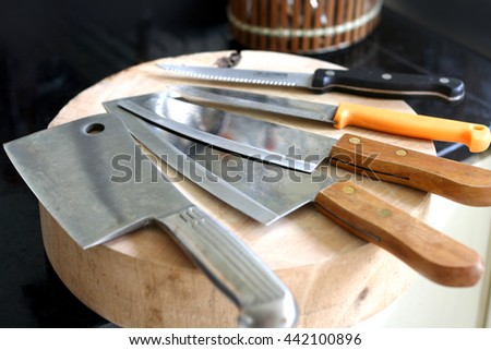 Kitchen knifes on chopping wood - stock photo