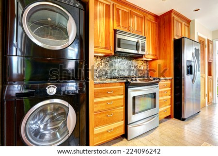 Kitchen maple storage combination with steel kitchen appliances and black laundry appliances - stock photo