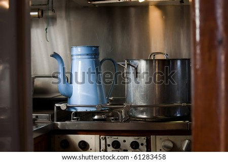 "Kitchen on board a very old wooden galley with an old ""madam blue"" coffea pot on the stove - stock photo"
