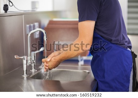 Kitchen porter washing his hands in professional kitchen - stock photo