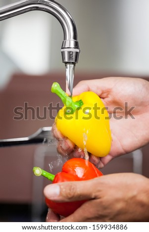 Kitchen porter washing red and yellow pepper under running tap in professional kitchen