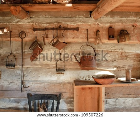 kitchen rack and utensils of a log cabin of the 1800s - stock photo